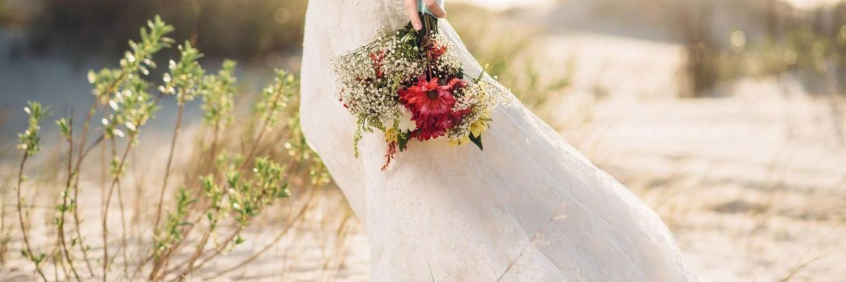 Bride walking through sand with flowers