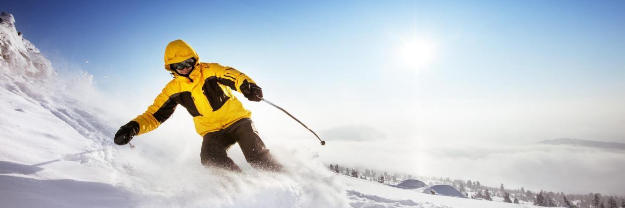 Skifahrer carvt gelbe Jacke Schnee.jpg