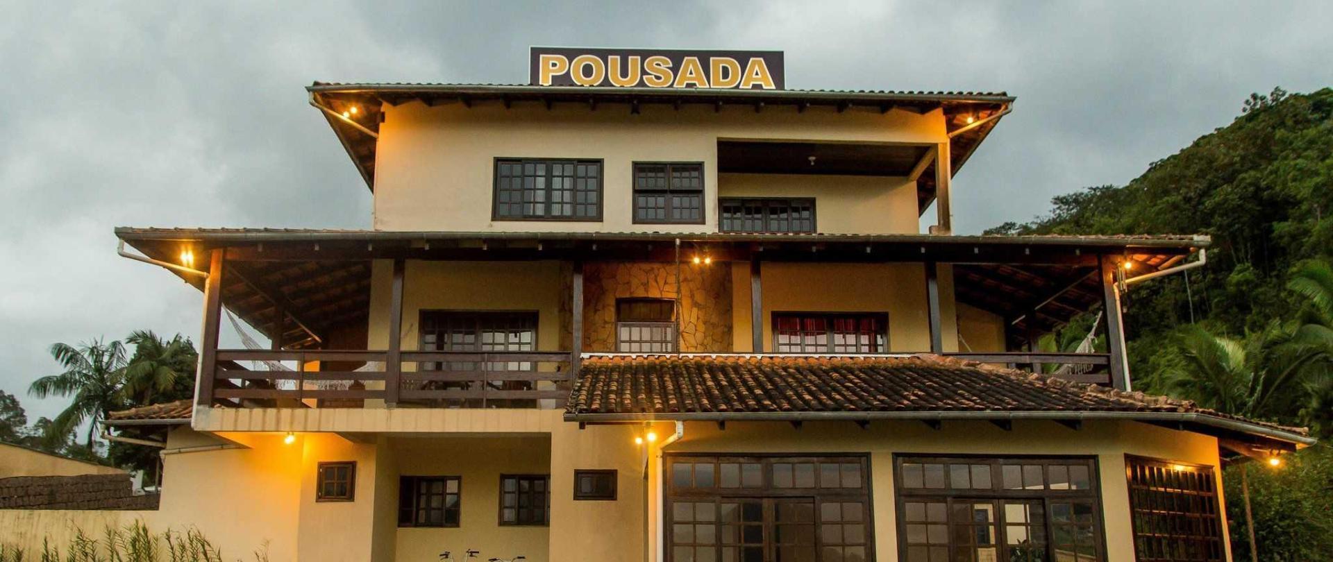 pousada-casar-o-em-jaragu-do-sul-santa-catarina-brasil-estacionamento-com-vista-da-cidade-e-das-montanhas-vista-frontal-dos-quartos-diurna.jpg
