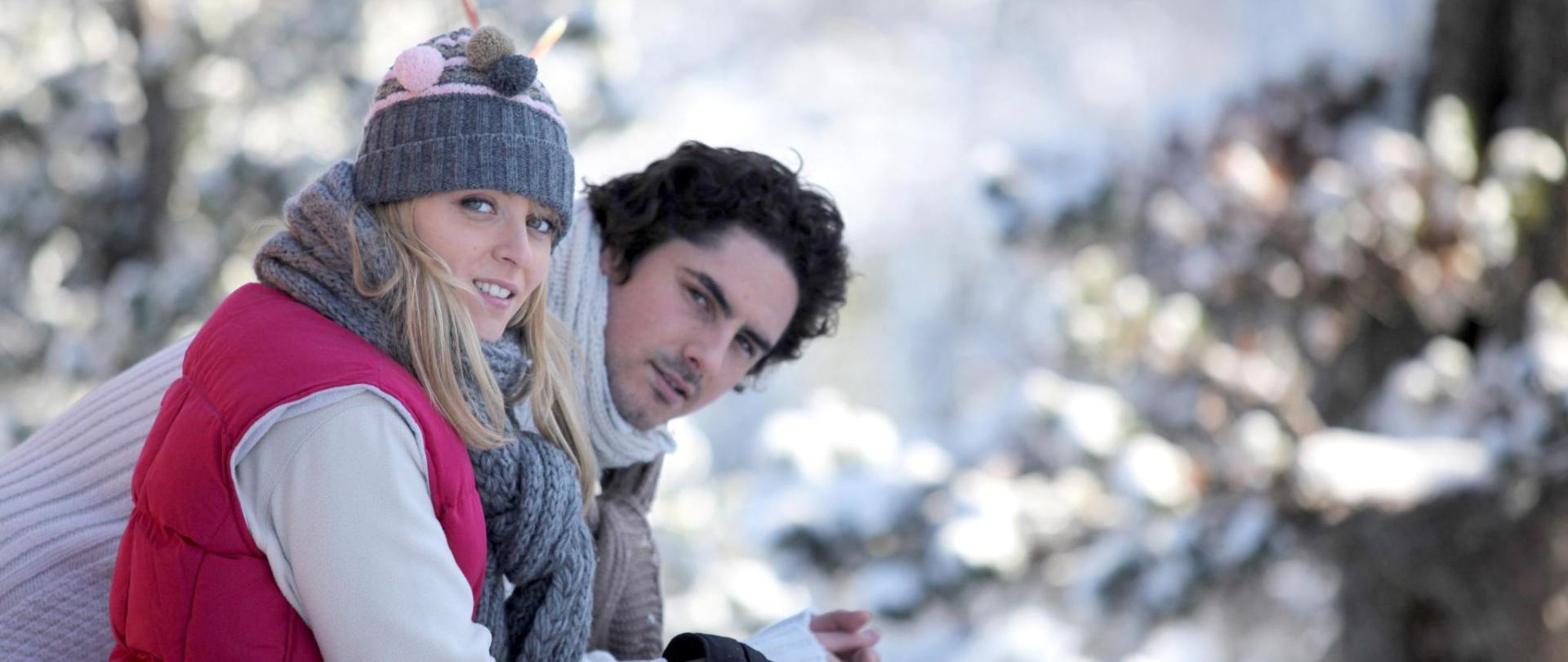 Paar mit gemütlichen dicken Stricksachen im Schnee.jpg