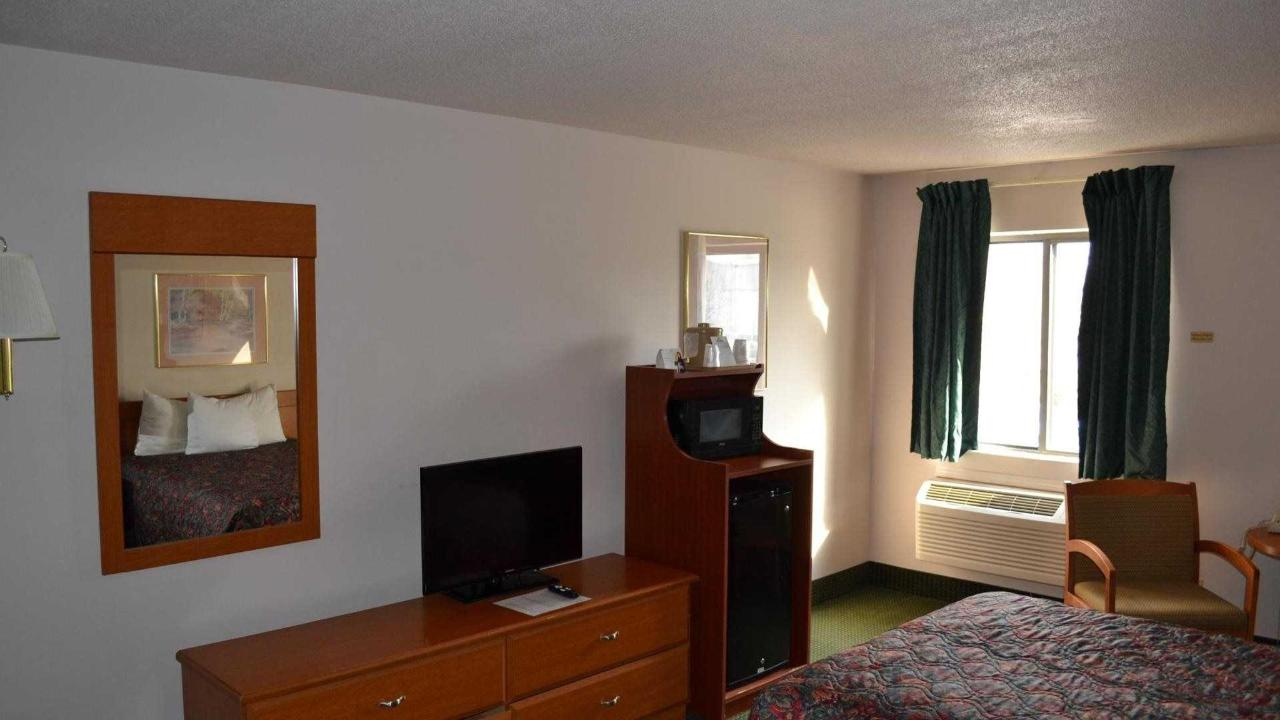 One bed room with sitting area, flat screen tv, microwave and refrigerator.jpg