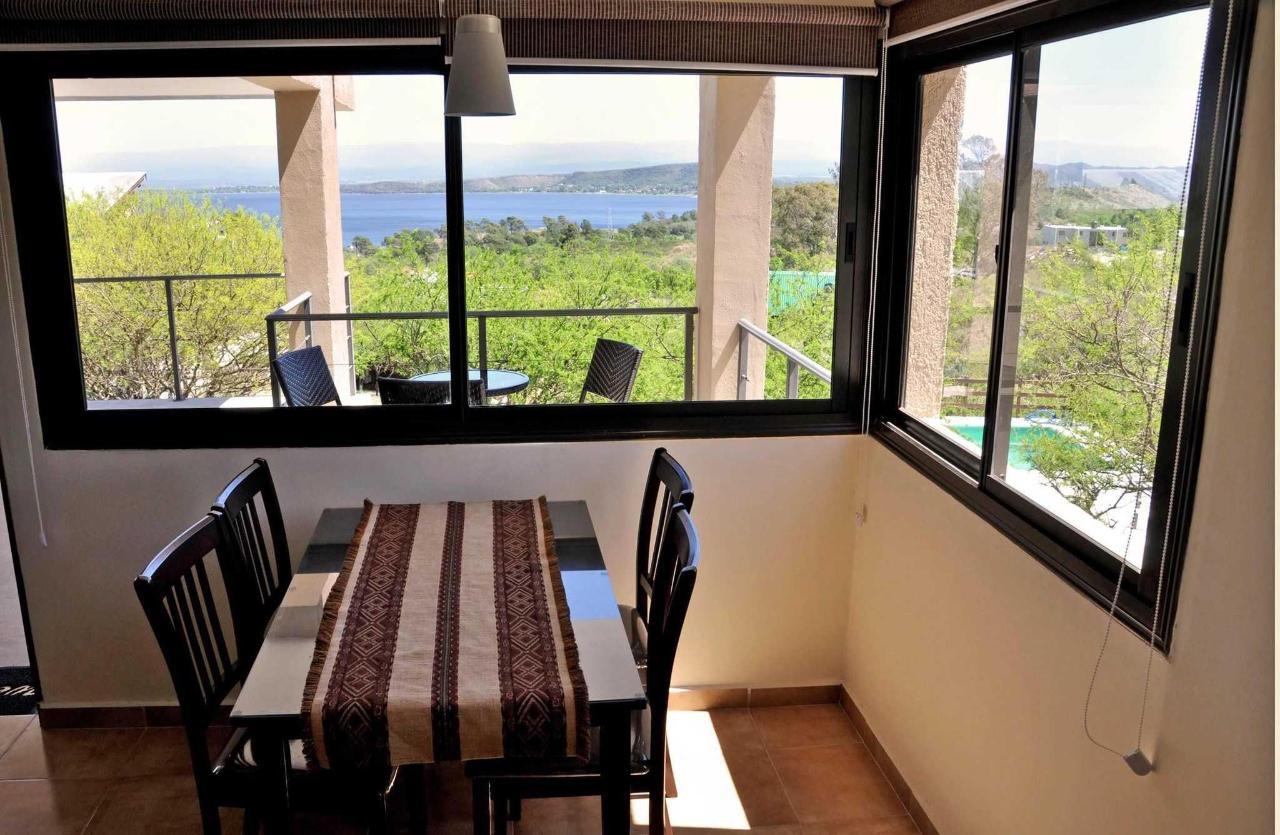 Comedor y galería balcón de departamentos con vista a la pileta, las sierras y el lago
