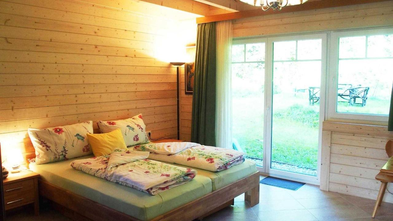 doublebed in the gardenroom with view in the forest