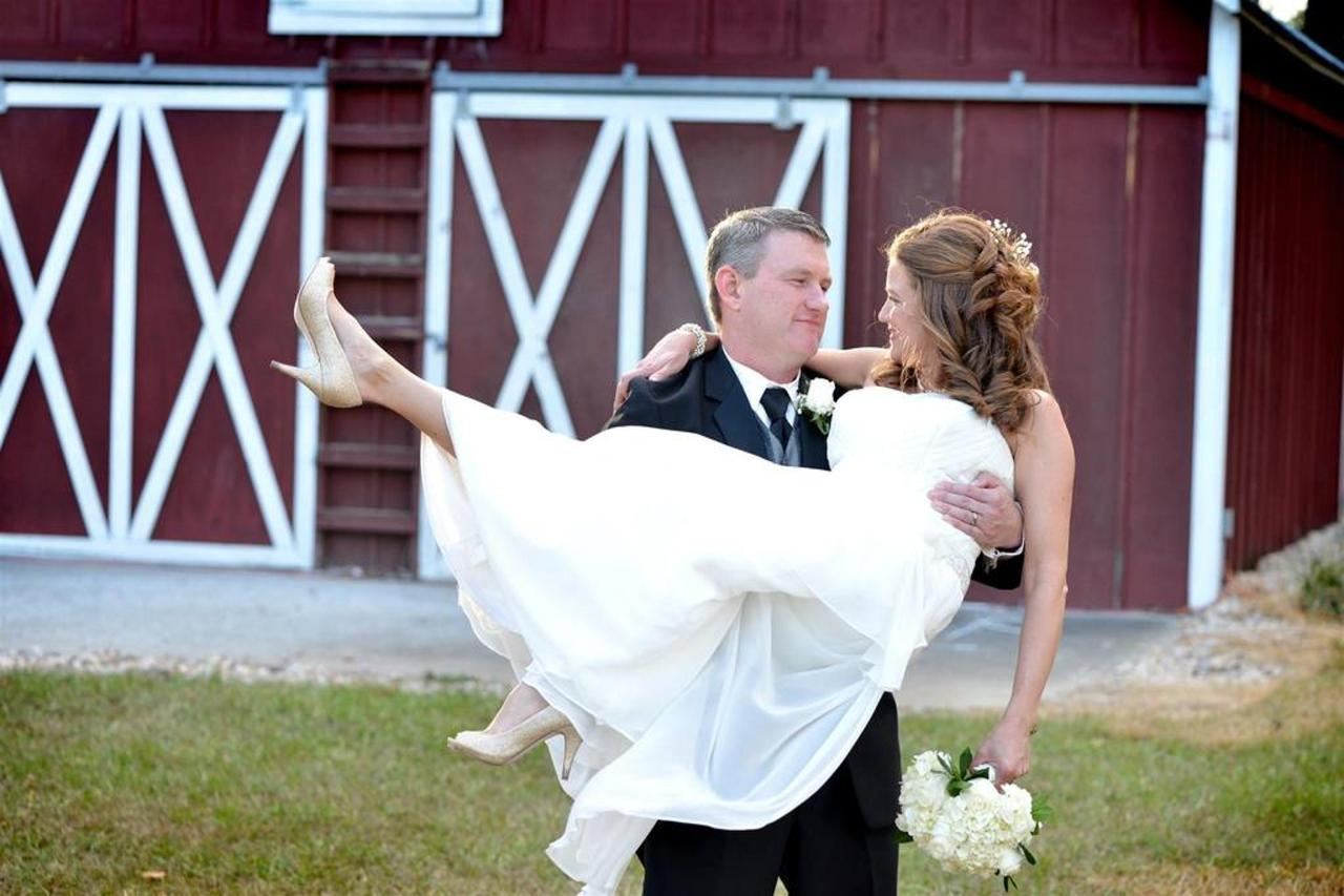 wedding-groom-holding-bride-pic-in-front-of-barn.jpg.1024x0.jpg